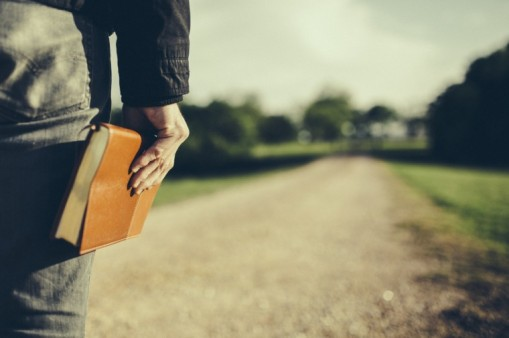man-holding-a-Bible-at-his-side-looking-down-a-long-dirt-road-Travis-Hallmark-760x506.2451246_std