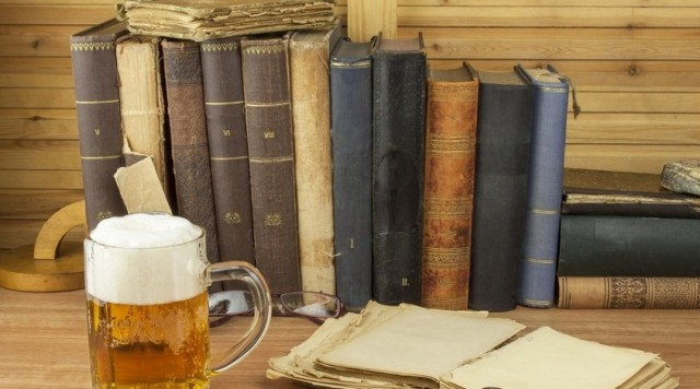 Cool glass of beer on the table. Relax with a good book with a g
